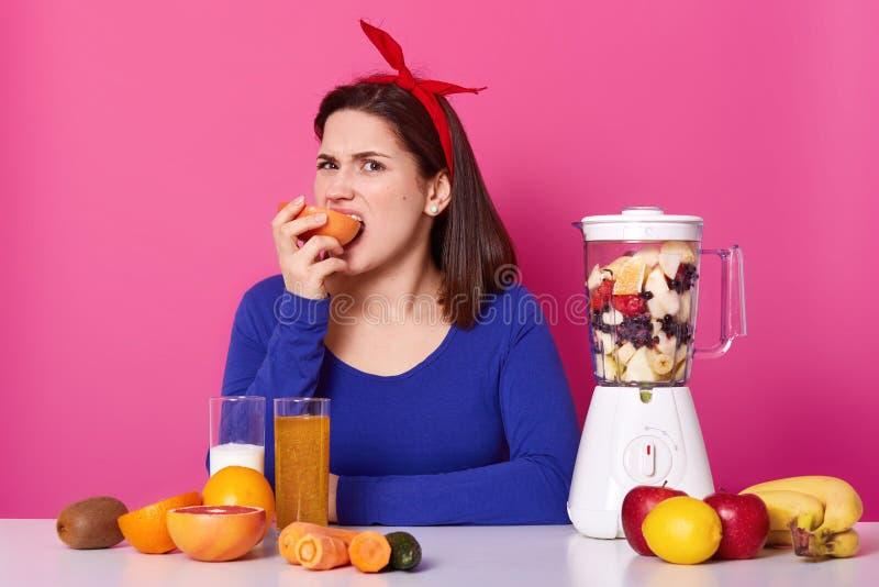Η χαρισματική νέα γυναίκα, φορά φωτεινό κόκκινο headband και το μπλε πουλόβερ, δαγκώνει και τρώει το γκρέιπφρουτ, δοκιμάζει μη κα στοκ φωτογραφία με δικαίωμα ελεύθερης χρήσης