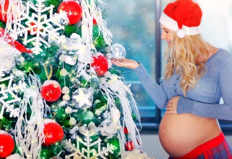 Η χαριτωμένη έγκυος γυναίκα εξωραΐζει το χριστουγεννιάτικο δέντρο στοκ φωτογραφία