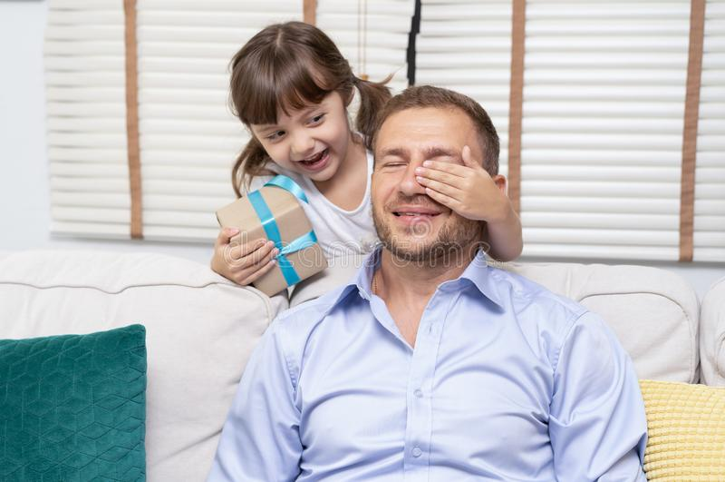 Η χαριτωμένη έκπληξη μικρών κοριτσιών δίνει το κιβώτιο δώρων πατέρων της στο σπίτι στοκ φωτογραφία