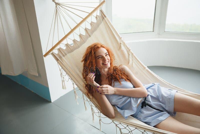 Η χαριτωμένη γελώντας νέα redhead κυρία βρίσκεται στην αιώρα στο εσωτερικό στοκ εικόνες με δικαίωμα ελεύθερης χρήσης
