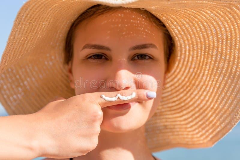 Η χαριτωμένη γυναίκα θέτει με το moustache που σύρεται με την κρέμα ήλιων στο δάχτυλό της κάτω από τη μύτη της στο υπόβαθρο θάλασ στοκ φωτογραφία με δικαίωμα ελεύθερης χρήσης