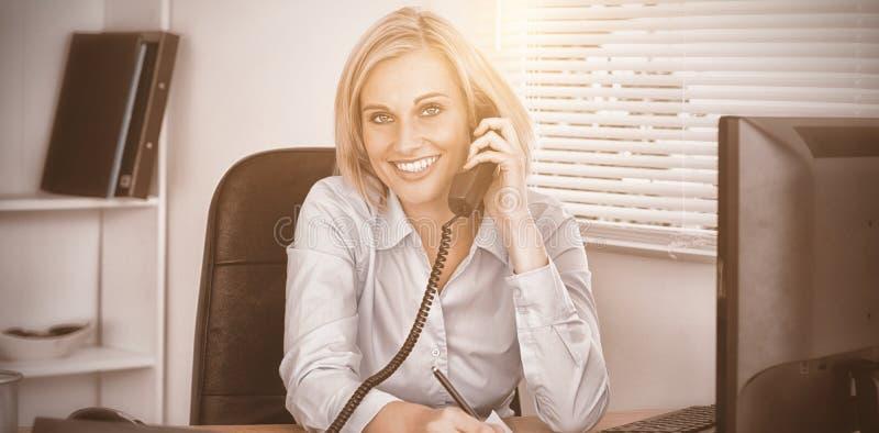 Η χαριτωμένη επιχειρηματίας στο τηλέφωνο που γράφει κάτι εξετάζει κάτω τη κάμερα στοκ εικόνες
