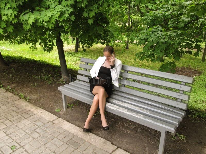 Η χαριτωμένη λεπτή γυναίκα σε ένα επιχειρησιακό κοστούμι κάθεται σε έναν πάγκο στο πάρκο με ένα lap-top και μιλά τηλεφωνικώς Ένα  στοκ φωτογραφία με δικαίωμα ελεύθερης χρήσης