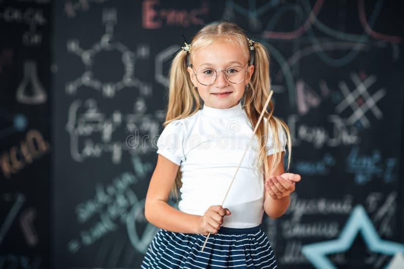 Η χαριτωμένη μαθήτρια με τα γυαλιά και να μοιάσουν κυβερνητών με έναν ακριβή δάσκαλο αύξησαν το δείκτη της για να επιστήσουν την  στοκ φωτογραφίες με δικαίωμα ελεύθερης χρήσης