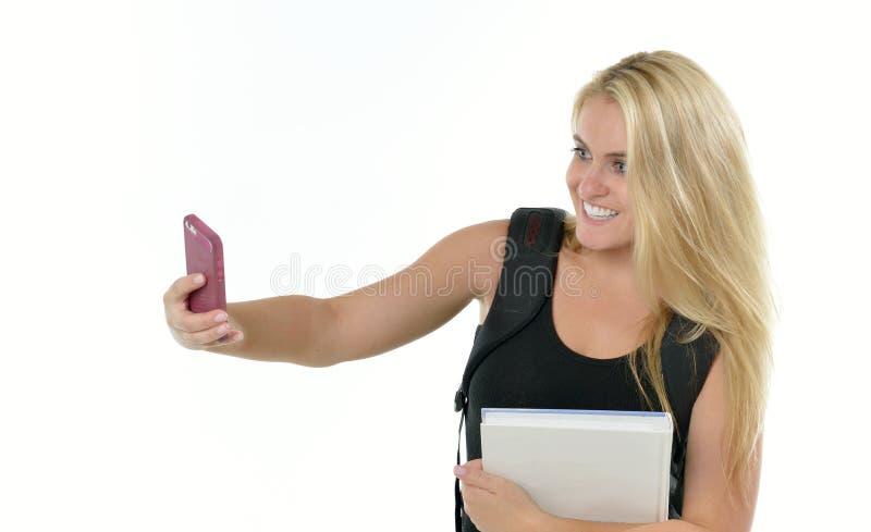 Η χαριτωμένη ξανθή γυναίκα σπουδαστής παίρνει ένα selfie στοκ εικόνες