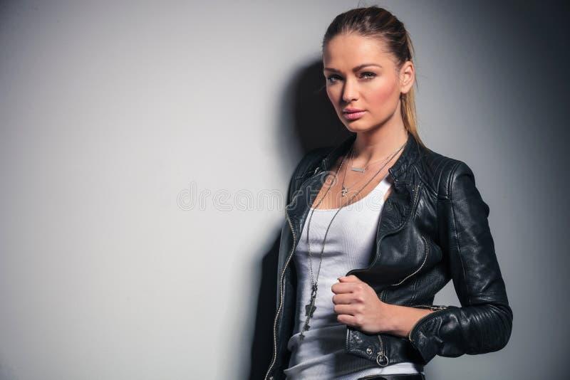 Η χαριτωμένη ξανθή γυναίκα στο σακάκι δέρματος κρατά το περιλαίμιό της στοκ εικόνες με δικαίωμα ελεύθερης χρήσης