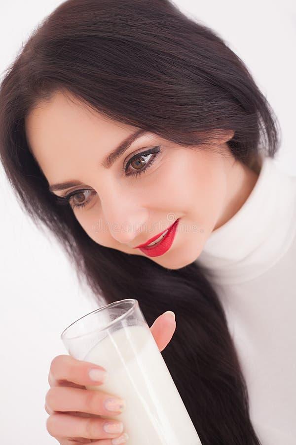 Η χαριτωμένη υγιής γυναίκα είναι πόσιμο γάλα από ένα γυαλί που απομονώνεται στο άσπρο υπόβαθρο στοκ εικόνες