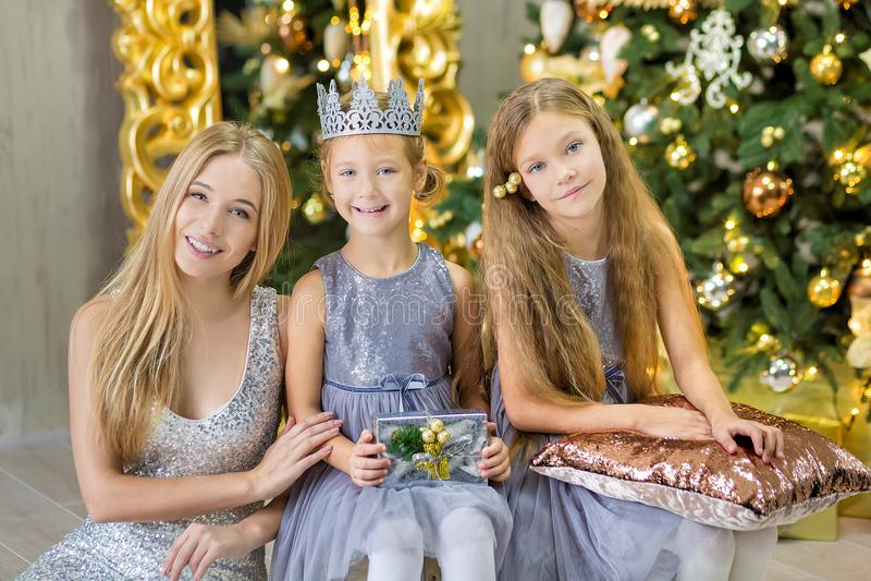 Η Χαρούμενα Χριστούγεννα και καλές διακοπές χαριτωμένα κορίτσια λίγων παιδιών που διακοσμούν το άσπρο πράσινο χριστουγεννιάτικο δ στοκ φωτογραφία