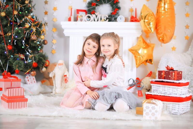 Η Χαρούμενα Χριστούγεννα και καλές διακοπές χαριτωμένος λίγο κορίτσι παιδιών διακοσμεί το χριστουγεννιάτικο δέντρο στο εσωτερικό στοκ φωτογραφίες