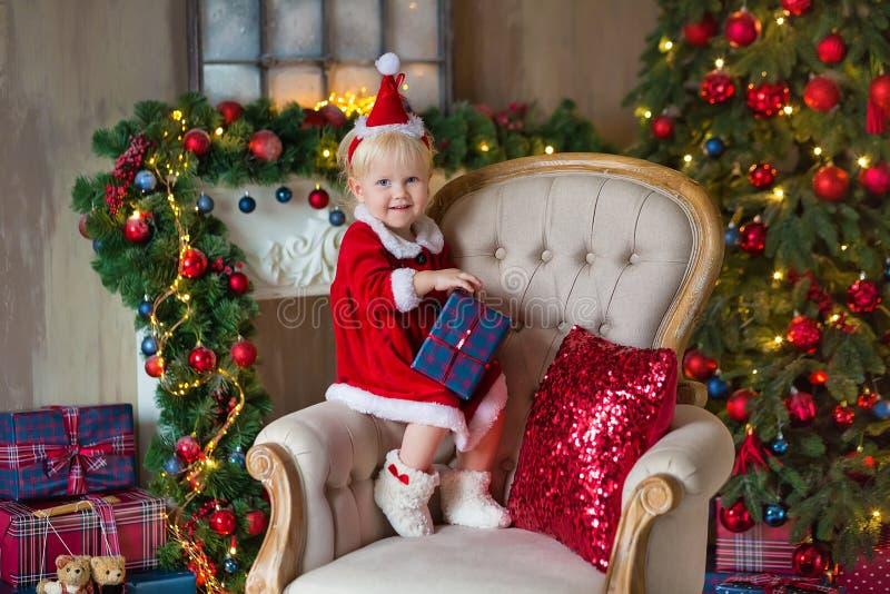 Η Χαρούμενα Χριστούγεννα και καλές διακοπές χαριτωμένος λίγο κορίτσι παιδιών διακοσμεί το χριστουγεννιάτικο δέντρο στο εσωτερικό στοκ εικόνες με δικαίωμα ελεύθερης χρήσης