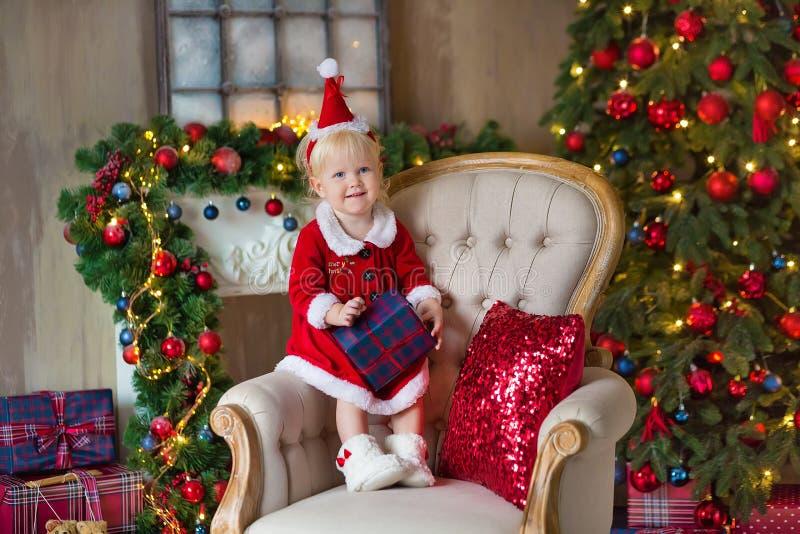 Η Χαρούμενα Χριστούγεννα και καλές διακοπές χαριτωμένος λίγο κορίτσι παιδιών διακοσμεί το χριστουγεννιάτικο δέντρο στο εσωτερικό στοκ εικόνες