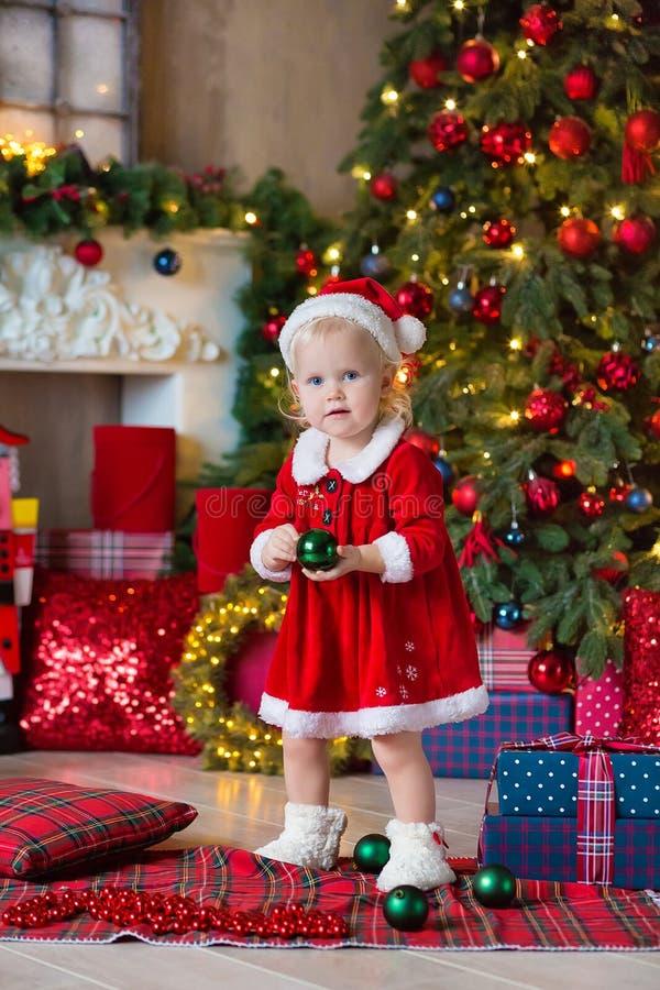 Η Χαρούμενα Χριστούγεννα και καλές διακοπές χαριτωμένος λίγο κορίτσι παιδιών διακοσμεί το χριστουγεννιάτικο δέντρο στο εσωτερικό στοκ φωτογραφία με δικαίωμα ελεύθερης χρήσης
