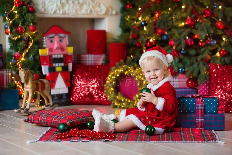 Η Χαρούμενα Χριστούγεννα και καλές διακοπές χαριτωμένος λίγο κορίτσι παιδιών διακοσμεί το χριστουγεννιάτικο δέντρο στο εσωτερικό στοκ εικόνα με δικαίωμα ελεύθερης χρήσης