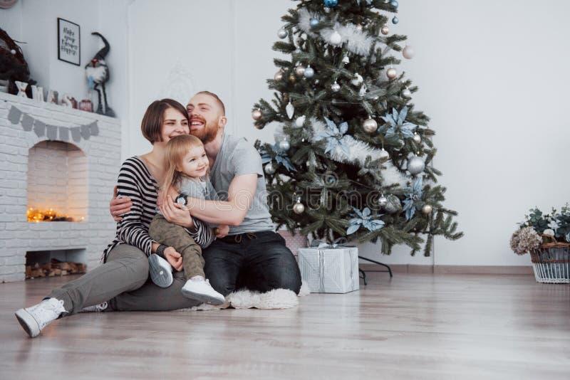 Η Χαρούμενα Χριστούγεννα και το όμορφο mom καλής χρονιάς, ο μπαμπάς και η κόρη χρησιμοποιούν ένα lap-top και χαμογελούν καθμένος  στοκ φωτογραφία με δικαίωμα ελεύθερης χρήσης