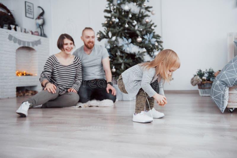 Η Χαρούμενα Χριστούγεννα και το όμορφο mom καλής χρονιάς, ο μπαμπάς και η κόρη χρησιμοποιούν ένα lap-top και χαμογελούν καθμένος  στοκ φωτογραφίες με δικαίωμα ελεύθερης χρήσης