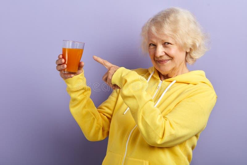 Η χαρούμενη ηλικιωμένη κυρία στον κίτρινο αθλητισμό hoodie προτιμά την υγιή κατανάλωση και τον ενεργό τρόπο ζωής στοκ εικόνες
