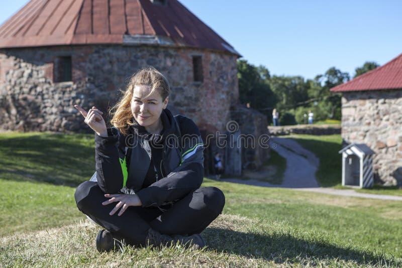Η χαρούμενη καυκάσια γυναίκα στο σακάκι μοτοσικλετών, γόνατο φρουρεί το κάθισμα στο πράσινο λιβάδι σε κάποιο ορόσημο, copyspace στοκ εικόνα με δικαίωμα ελεύθερης χρήσης