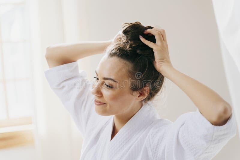Η χαρούμενη νεαρή γυναίκα ευθυγραμμίζει τα μαλλιά της στοκ εικόνες