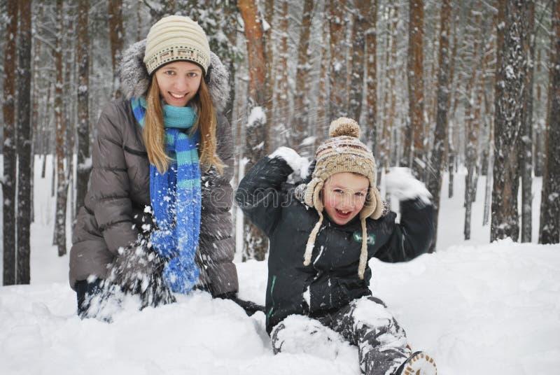 Η χειμερινή μητέρα με το γιο της επιτρέπει τη συνεδρίαση στο χιόνι στο wo στοκ εικόνες με δικαίωμα ελεύθερης χρήσης
