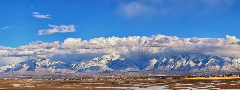 Η χειμερινή πανοραμική άποψη του χιονιού κάλυψε τα μπροστινά δύσκολα βουνά Wasatch, την κοιλάδα του Γκρέιτ Σωλτ Λέηκ και Cloudsca στοκ φωτογραφία