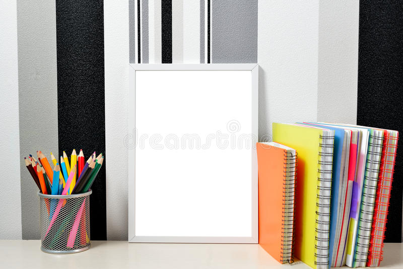Η χλεύη πλαισίων αφισών επάνω στο πρότυπο με τα χρωματισμένα σημειωματάρια και μπορεί με τα μολύβια στον ξύλινο πίνακα στοκ εικόνα