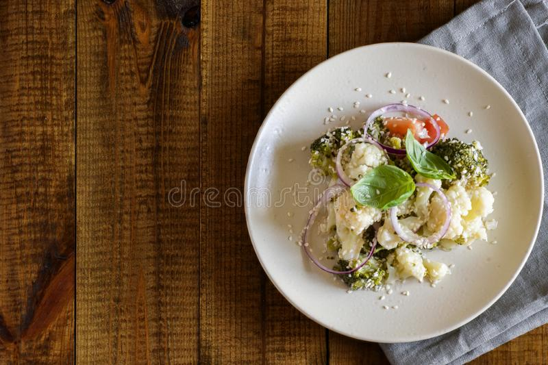 Η χορτοφάγος σαλάτα του μπρόκολου, το κουνουπίδι, οι ώριμες ντομάτες, τα γλυκά κρεμμύδια, ο βασιλικός και το σουσάμι σε μια όμορφ στοκ φωτογραφία