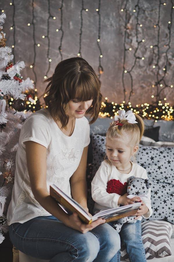 Η χρονών κόρη μητέρων διάβασε το βιβλίο στις διακοσμήσεις Χριστουγέννων στοκ εικόνα