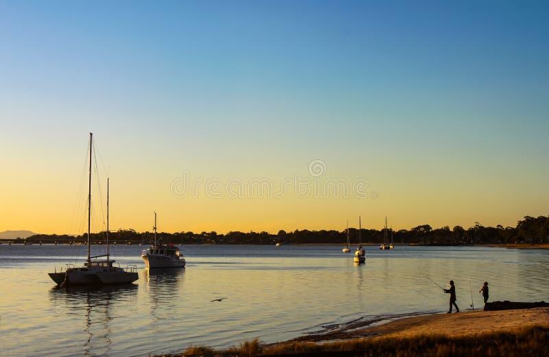 Η χρυσή ώρα με τους ψαράδες και τις βάρκες έδεσε στο λιμάνι και ένα χαμηλό πετώντας πουλί στο νησί Αυστραλία Bribie στοκ εικόνες