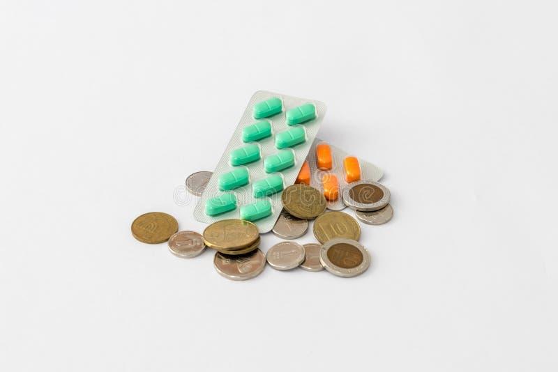 Η χρωματισμένη στενόμακρη μορφή χαπιών σε μια συσκευασία εναπόκειται στα ισραηλινά νομίσματα σε ένα άσπρο υπόβαθρο στοκ εικόνα με δικαίωμα ελεύθερης χρήσης