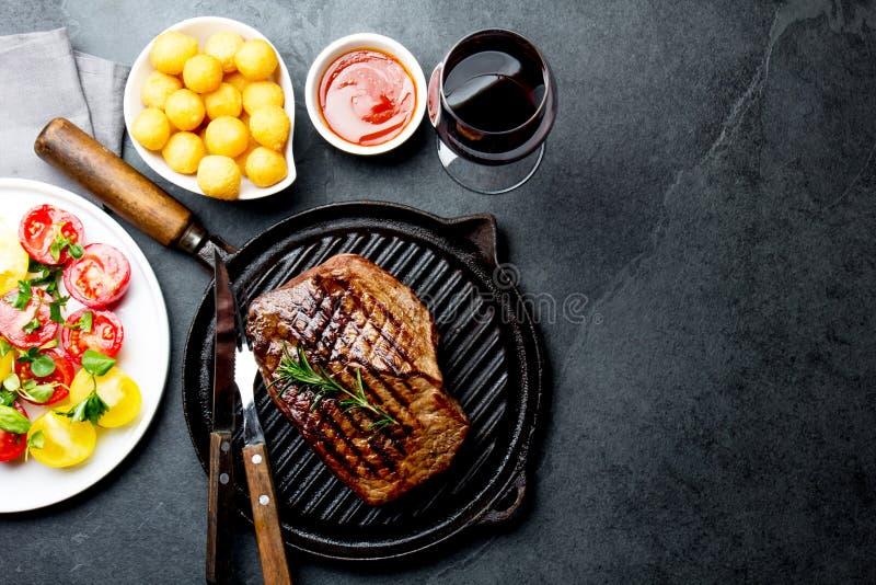 Η ψημένη στη σχάρα μπριζόλα βόειου κρέατος στο τηγάνι σχαρών εξυπηρέτησε με τη σαλάτα ντοματών, τις σφαίρες πατατών και το κρασί  στοκ εικόνες με δικαίωμα ελεύθερης χρήσης
