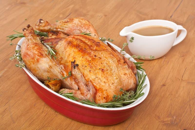 Η ψημένη Rosemary Τουρκία σε ένα πιάτο με το ζωμό στοκ εικόνα