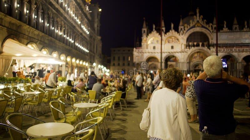 Η ψυχαγωγία νύχτας για τους τουρίστες στο φωτισμένο ST χαρακτηρίζει το τετράγωνο, γύρος στη Βενετία στοκ φωτογραφία