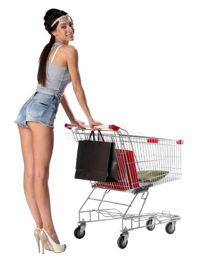 Η όμορφα γυναίκα brunette και το καροτσάκι αγορών με αγορές τοποθετούν σε σάκκο στοκ εικόνες