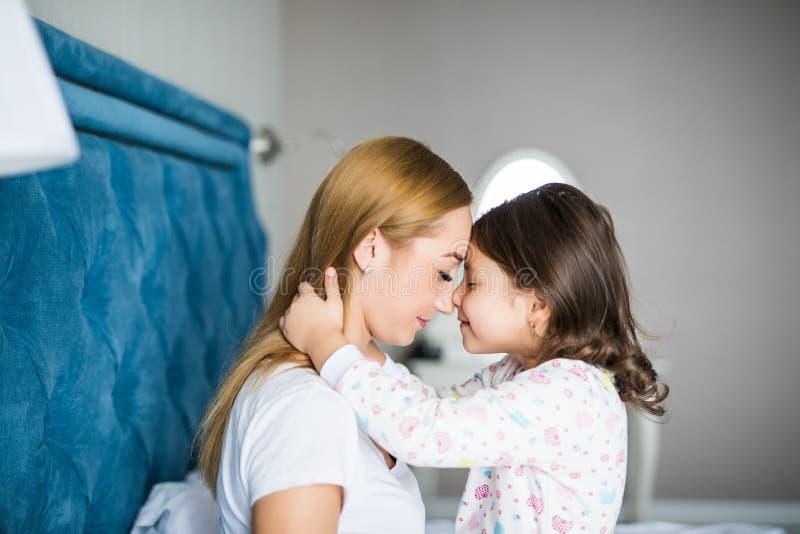 Η όμορφες νέες γυναίκα και που γοητεύουν λίγη κόρη αγκαλιάζουν και χαμογελούν στο κρεβάτι στο σπίτι στοκ εικόνα με δικαίωμα ελεύθερης χρήσης