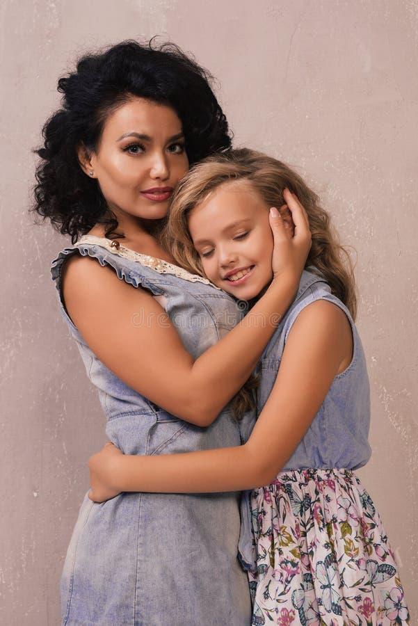 Η όμορφες νέες γυναίκα και που γοητεύουν λίγη κόρη αγκαλιάζουν και χαμογελούν στοκ εικόνες
