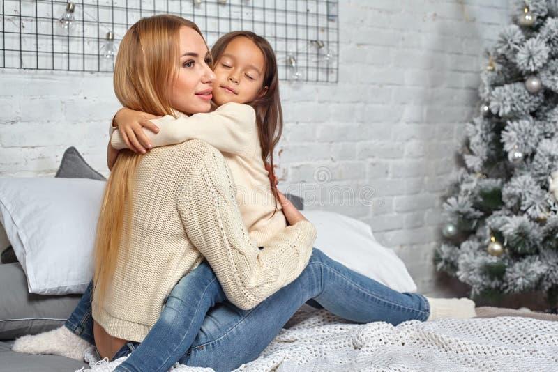 Η όμορφες νέες γυναίκα και που γοητεύουν λίγη κόρη αγκαλιάζουν στοκ φωτογραφία