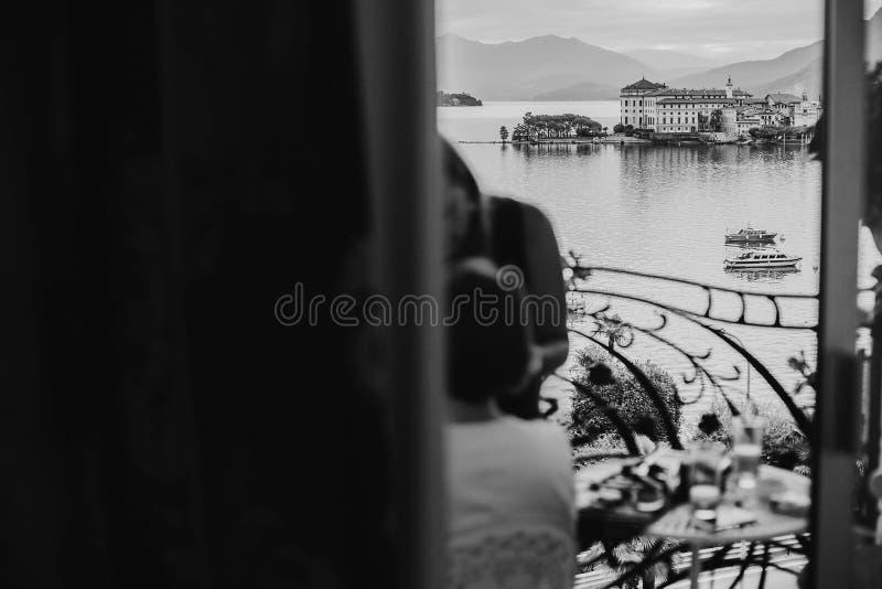 Η όμορφη άποψη σχετικά με τα νησιά Borromean από το παράθυρο μπαλκονιών στο δωμάτιο ξενοδοχείου ήταν μοντέρνη νύφη που παίρνει το στοκ φωτογραφίες