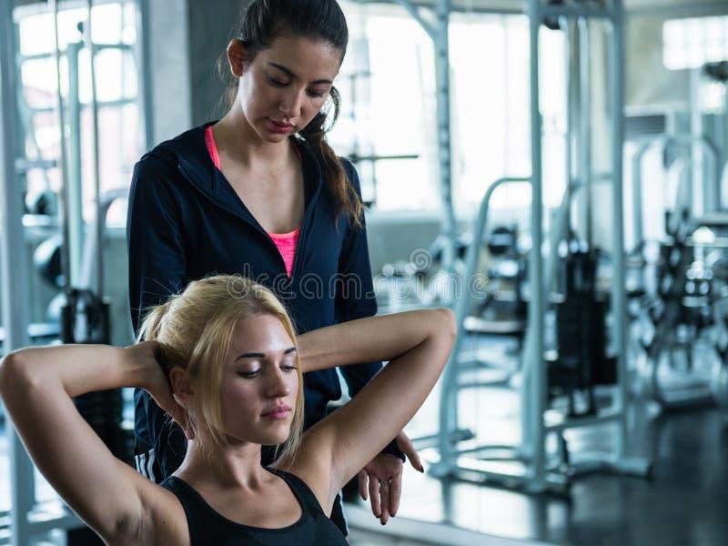 Η όμορφη άσκηση γυναικών ακολουθεί την οδηγία του εκπαιδευτή στη GY στοκ φωτογραφία