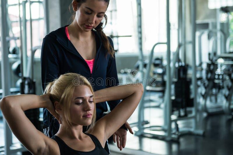 Η όμορφη άσκηση γυναικών ακολουθεί την οδηγία του εκπαιδευτή στη GY στοκ εικόνα