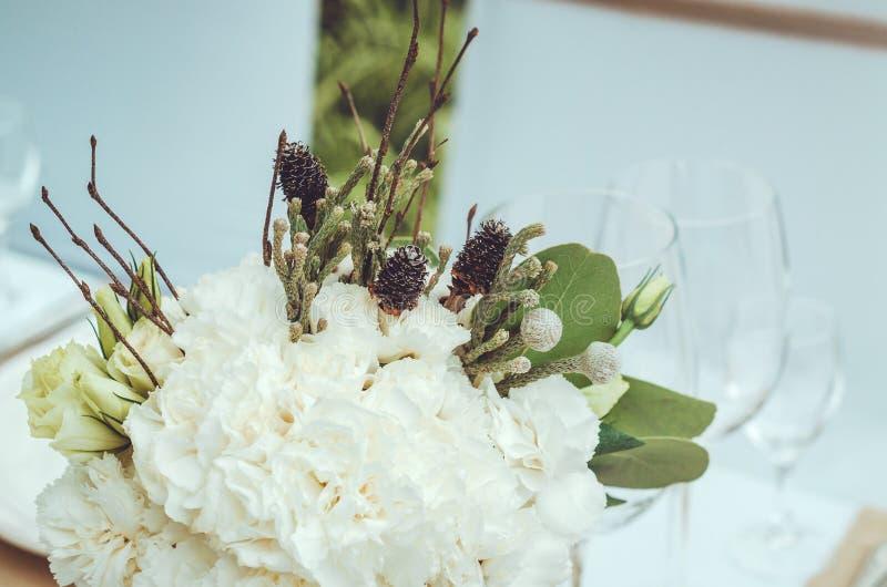 Η όμορφη άσπρη ανθοδέσμη των γαρίφαλων, κώνοι, τριαντάφυλλα ανθίζει στο βάζο στο υπόβαθρο επιτραπέζιων τεχνών Γεγονός χειμερινού  στοκ εικόνες