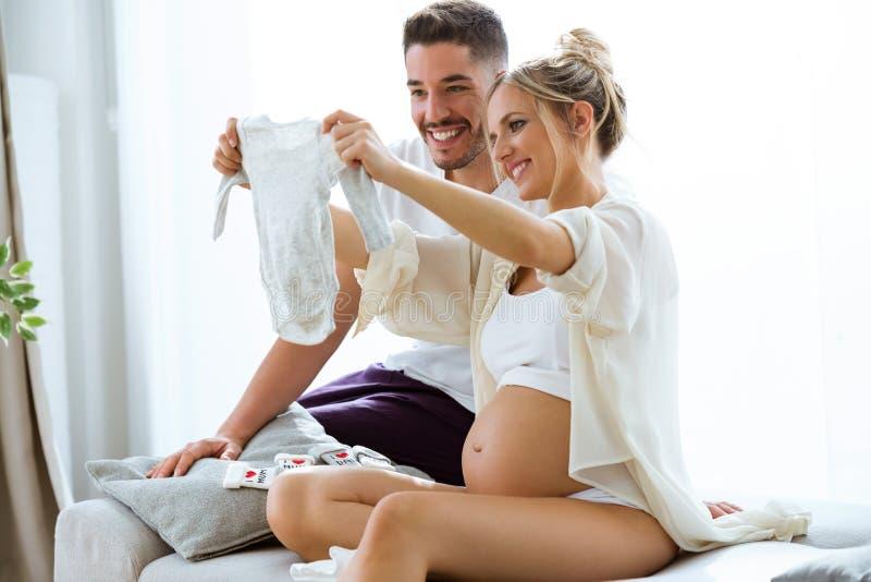 Η όμορφη έγκυος γυναίκα και ο σύζυγός της φαίνονται ενδύματα μωρών στον καναπέ στο σπίτι στοκ εικόνα με δικαίωμα ελεύθερης χρήσης