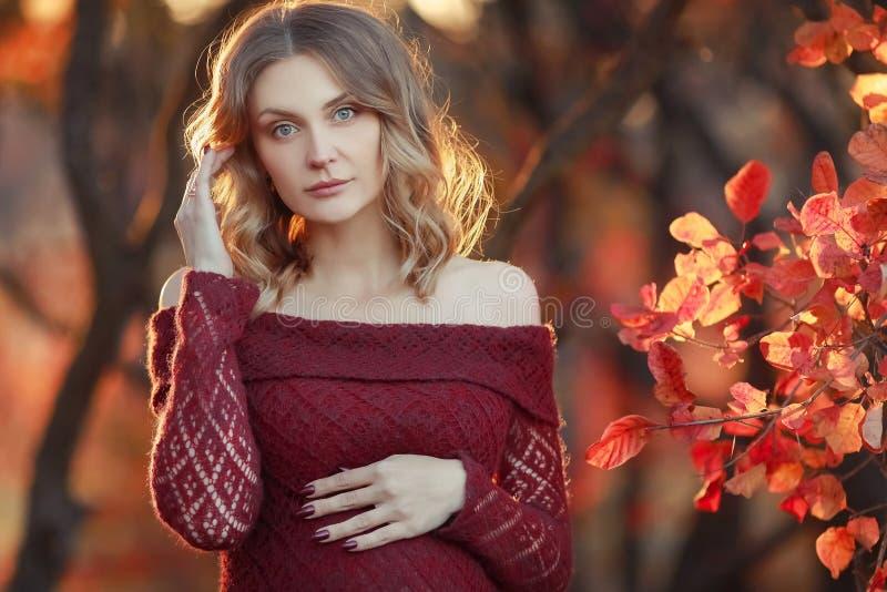 Η όμορφη έγκυος γυναίκα με τα ξανθά μαλλιά στο πολύ κόκκινο φόρεμα και το λαμπρό περιδέραιο στέκεται στο δάσος, χαμογελώντας ήπια στοκ φωτογραφία
