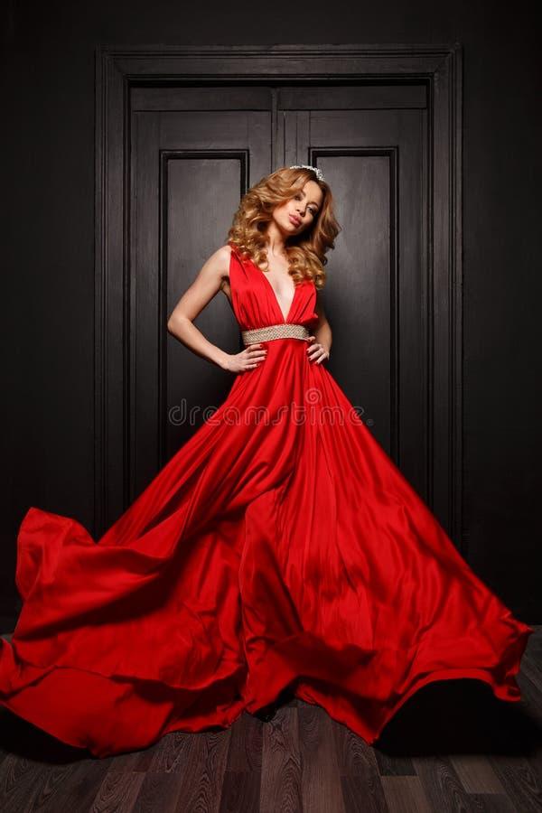Η όμορφη έξυπνη ντυμένη γυναίκα στο κόκκινο κυματίζοντας φόρεμα βραδιού θέτει, η ξύλινη πόρτα είναι στο υπόβαθρο στοκ εικόνες