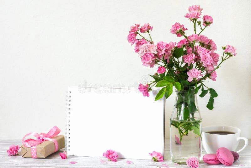 Η όμορφη ανθοδέσμη των ρόδινων τριαντάφυλλων ανθίζει, φλυτζάνι καφέ, macaroons, κιβώτιο δώρων και κενή άσπρη ευχετήρια κάρτα Χλεύ στοκ εικόνα