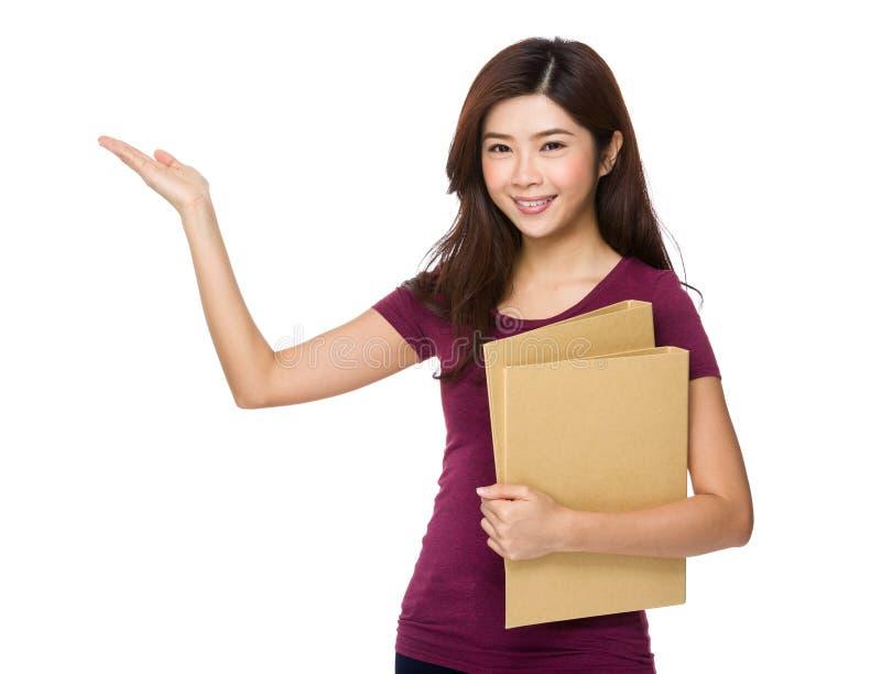 Η όμορφη ασιατική γυναίκα με την εργασία εγγράφων και το χέρι παρουσιάζουν με μερικούς στοκ εικόνες