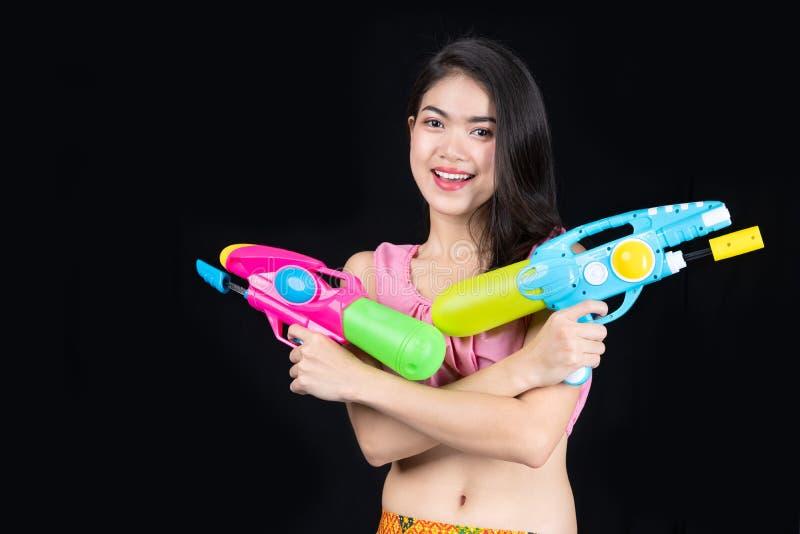 Η όμορφη ασιατική γυναίκα πορτρέτου παίρνει το πλαστικό πυροβόλο όπλο στο μαύρο υπόβαθρο κόμμα πυροβόλων όπλων νερού ή φεστιβάλ S στοκ φωτογραφίες