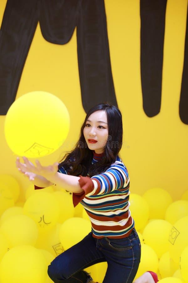 Η όμορφη ασιατική κινεζική νέα ευτυχής χαμογελώντας γυναίκα μόδας με τα κίτρινα μπαλόνια αέρα έχει τη διασκέδαση ρ στοκ φωτογραφία με δικαίωμα ελεύθερης χρήσης