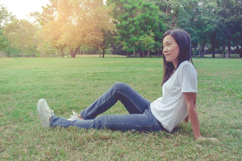 Η όμορφη ασιατική συνεδρίαση γυναικών και να βρεθούν χαλαρώνουν στον πράσινο τομέα λιβαδιών χλόης στο πάρκο Αυτή που αισθάνεται τ στοκ φωτογραφίες με δικαίωμα ελεύθερης χρήσης