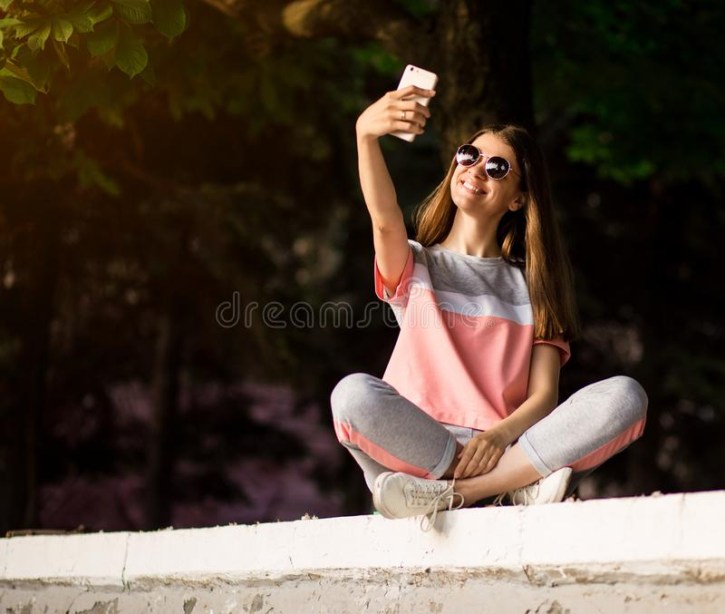 Η όμορφη αστική γυναίκα στα γυαλιά ηλίου καθιστά selfie το πορτρέτο υπαίθριο στη θερινή ημέρα στοκ φωτογραφία με δικαίωμα ελεύθερης χρήσης