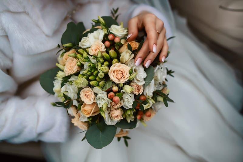 Η όμορφη γαμήλια ανθοδέσμη των άσπρων και ρόδινων λουλουδιών με τα πράσινα φύλλα στα χέρια της νύφης, θαυμασμός νυφών ανθίζει στοκ εικόνα